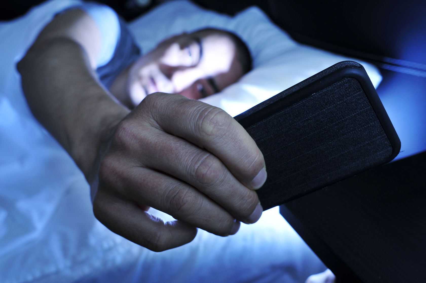 Closeup of a Young Man in Bed Looking at the Smartphone at Night Image