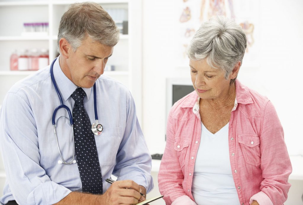 Woman Sitting Next to Her Doctor Image