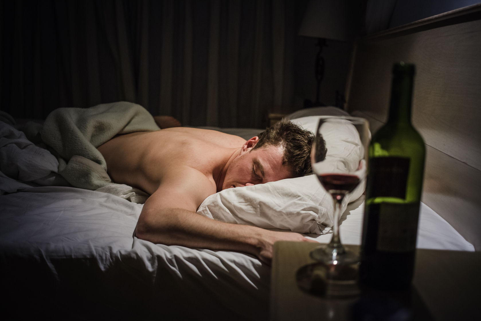 Lonely drunk man sleeping after a bottle of wine image