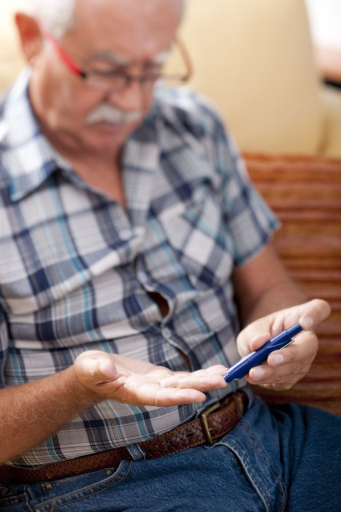 Man with Diabetes Testing His Blood Sugar Image