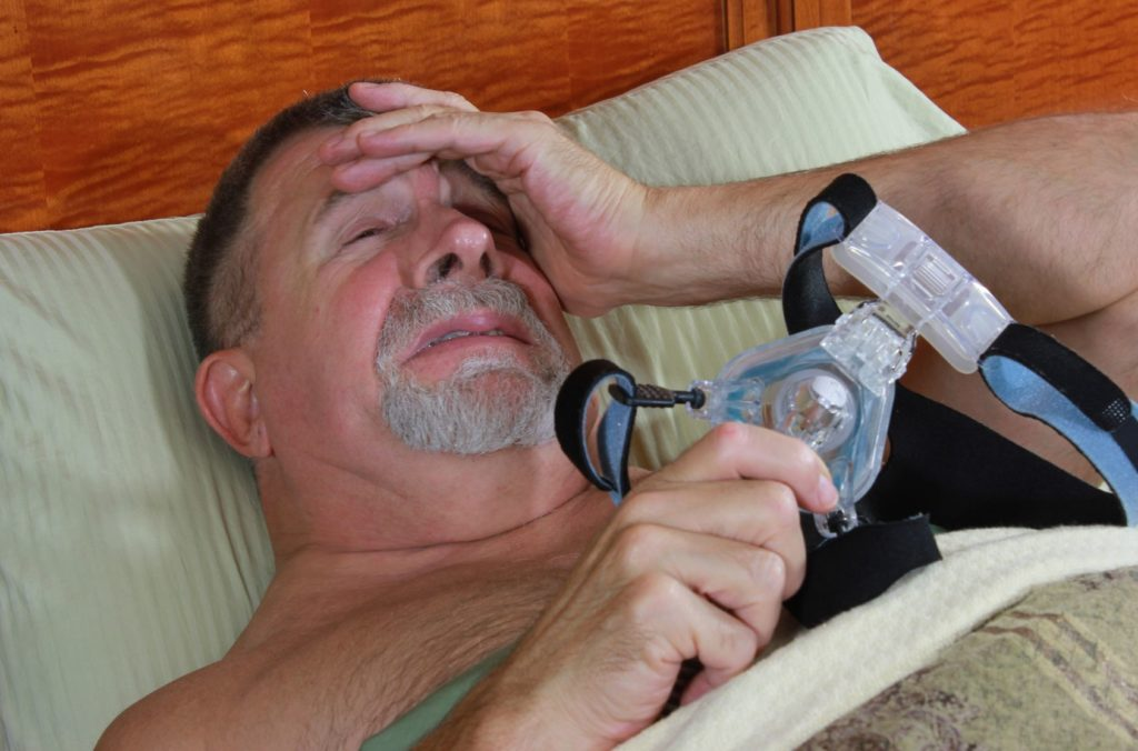Adult Man Frustrated with CPAP Mask Image