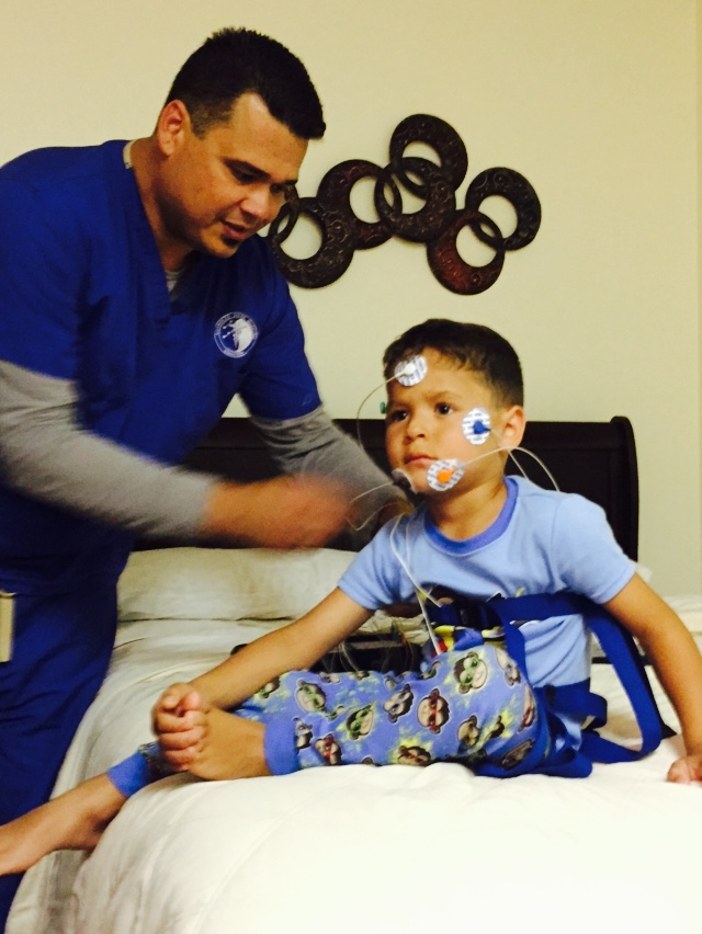 Sleep Technician Hooking up a Child for Sleep Study Image